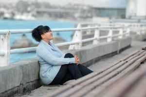 Ziele erreichen durch Intuition: Frau am Ufer schaut entspannt in den Himmel