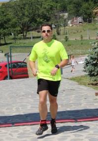 muž v zelenom drese dobieha do cieľa