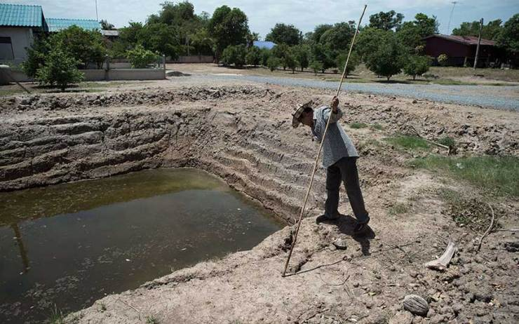 A-Thai-farmer-looking-at-a-nearly-dried-out-farm-pond,-which-is-usually-full,-in-Bang-Pla-Ma-district,-Suphanburi-province.