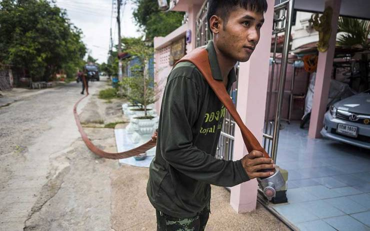 A-Thai-soldiers-carries-a-hose-to-deliver-water-to-a-home-in-Pathum-Thani-province,-no-Tap-water!