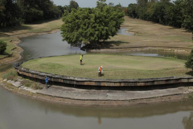 Workers tend to a green on a golf course in Khlong of Pathum Thani's Nong Sua district as the lake around the green continues to drop