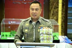 Police chief Somyot Poompunmuang shows the three million baht reward at a press conference on Monday as he announces it will be paid to the police team whose investigation led to the arrest of a suspect