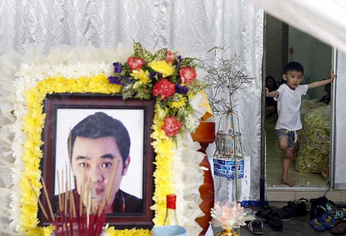 Stunned: Six-year-old Lee Jian Han looks at the coffins of his father Lee Tze Siang and his four-year-old sister