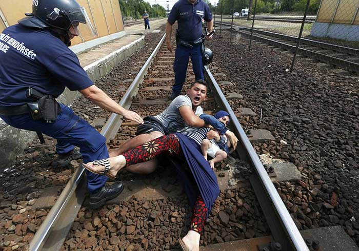 father-overcome-with-emotion-tries-desperately-to-protect-his-wife-and-child-from-being-taken-away-to-refugee-camp---lying-down-on-the-tracks-in-protest
