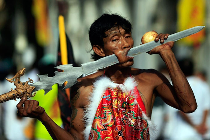 ATTENTION EDITORS - GRAPHIC CONTENT A devotee of the Chinese Bang Neow Shrine with a sword pierced through his cheek takes part in a street procession during the annual vegetarian festival in Phuket October 10, 2013. The festival, featuring face-piercing, spirit mediums, and strict vegetarianism celebrates the local Chinese community's belief that abstinence from meat and various stimulants during the ninth lunar month of the Chinese calendar will help them obtain good health and peace of mind. REUTERS/Athit Perawongmetha (THAILAND - Tags: RELIGION SOCIETY) TEMPLATE OUT