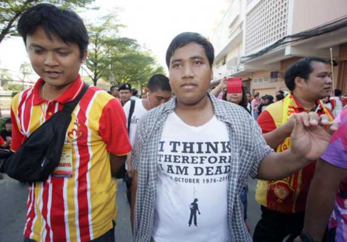'Not afraid': Student activist Sirawith 'Ja New' Seritiwat is escorted from the football match by yesterday by undercover authorities wearing Thammasat University shirts.