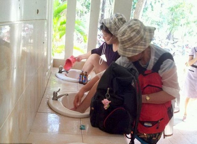 chinese-tourists-cleaning-their-feet-and-sandals-inside-a-bathroom-on-the-island-of-phi-phi-thailand