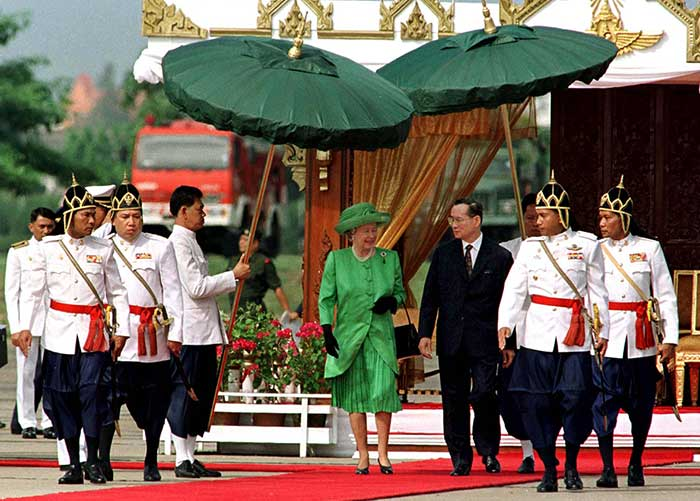28 October 1996: Royal guards shade Queen Elizabeth II and King Bhumibol Adulyadej from the sun during a welcoming ceremony at Bangkok military airport during the British royals' five-day visit to commemorate the 50th anniversary of the Thai king's accession to the throne