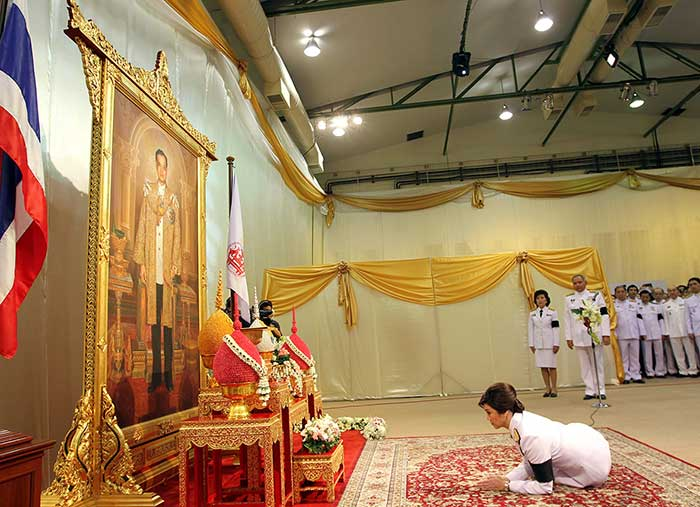 8 August 2011: Thailand's first female Prime Minister Yingluck Shinawatra prostrates herself before a portrait of King Bhumibol Adulyadej, as she receives the royal command