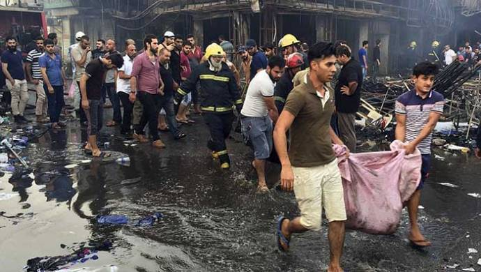 iraqi-firefighters-and-civilians-evacuate-bodies-of-victims-killed-after-a-car-bomb-went-off-in-baghdad-iraq