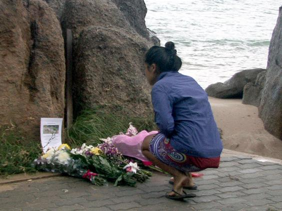 A Thai lays flowers during a memorial service for two murdered British tourists on Koh Tao island