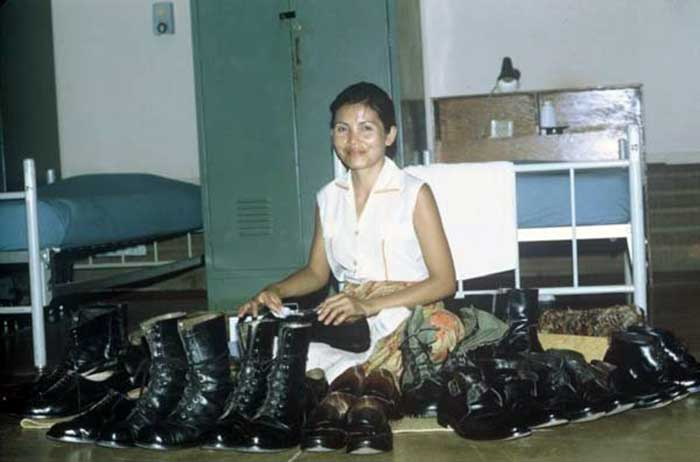 Old Pattaya- Thai lady is polishing the American soldiers boots