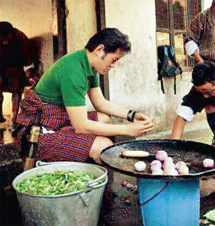 A-picture-of-the-king-chopping-onions-and-chillies-to-prepare-a-meal-for-the-Community-School-in-Mongar