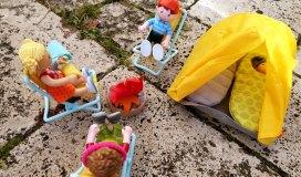 Little Friends sitzen am Lagerfeuer vor ihrem Zelt
