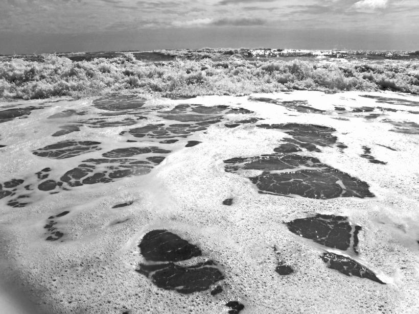 Foto in schwarz/weiß: Brandung am Strand. Schaum auf dem Wasser. Die nächste Welle kommt.