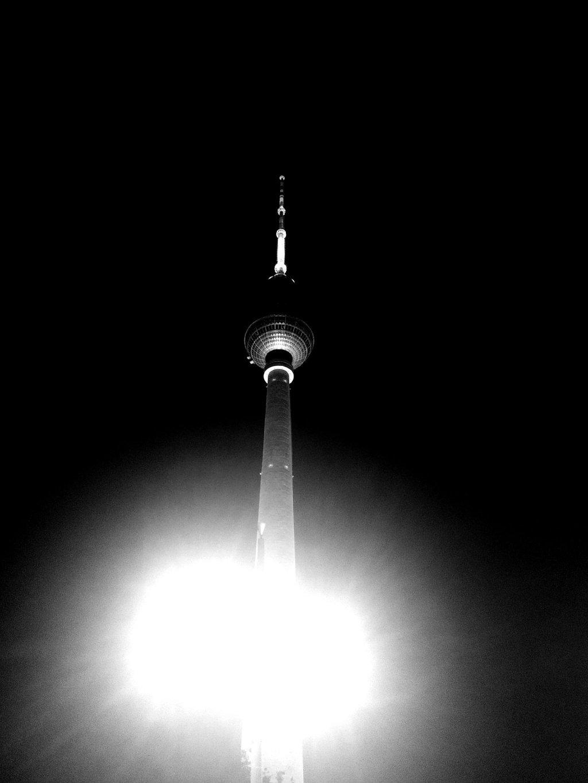 Foto in schwarz/weiß: Fernsehturm vor schwarzen Nachthimmel, im Vordergrund die beiden Lichtbälle einer Straßenlaterne