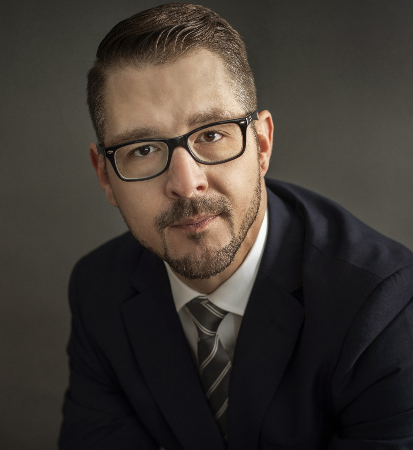 Headshot of Matthew R. Zwick, Esq. He is wearing a dark navy suit jacket, striped tie, white collared shirt and dark framed glasses.