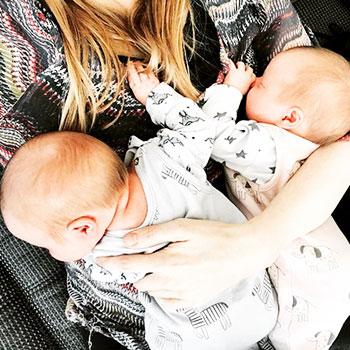 Zwillingsmama mit ihren eineiigen Zwillingen auf dem Arm.