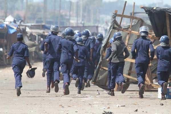 Armed Zimbabwe Republic Police officers shoot fleeing vendor