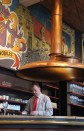 The bar at the Halve Maan brewery, featuring the top of a copper brewing kettle as a giant lampshade